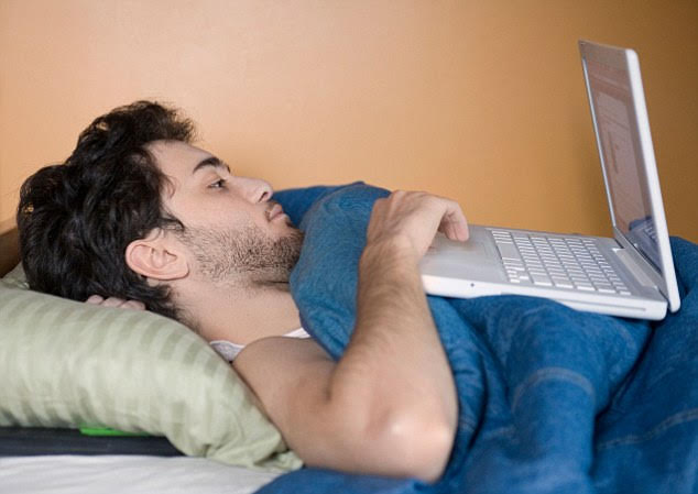 B893F8 A young man using his laptop computer while still lying in bed.