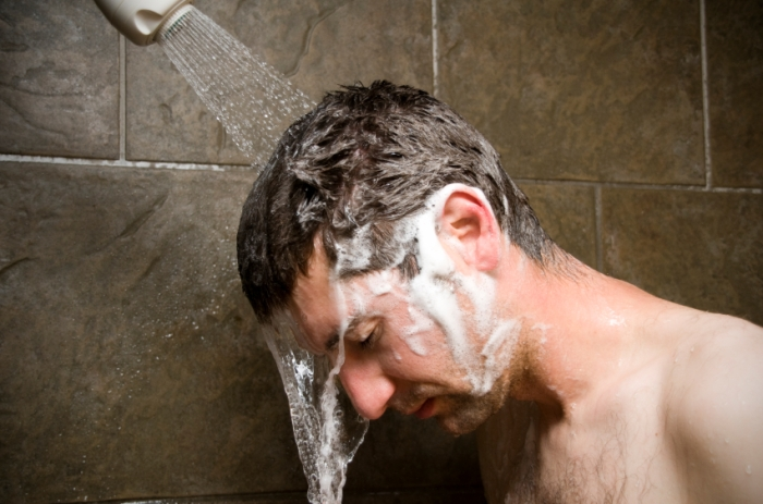 man-showering-water-washing-over-him
